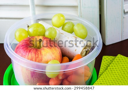Close up of plastic container with healthy school lunch.