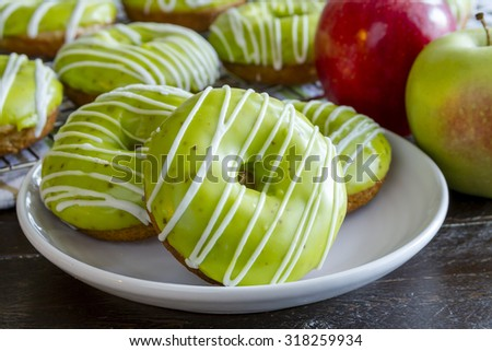 Close up of plate of homemade baked caramel apple donuts with green apple glaze sitting on white plate with fresh apples in background