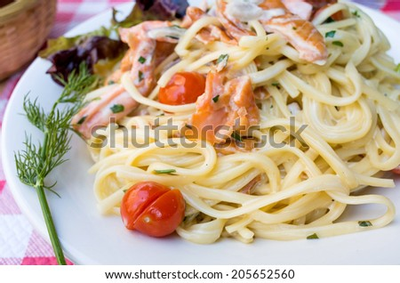 close-up of plate of pasta and smoked salmon with tomato