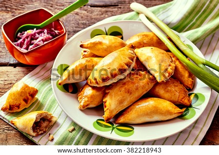 Close Up of Plateful of Fresh Baked Empanada Pastries with Fresh Green Onions and Cabbage Side Dish Served on Rustic Wooden Table with Copy Space