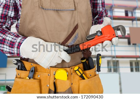 Close-up Of Plumber Holding Monkey Spanner With Worktool In Tool Bag - stock photo