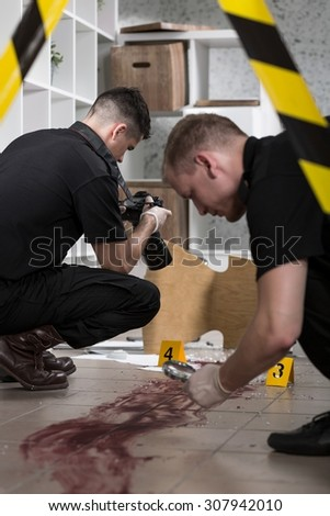 Close-up of policemen working at the murder scene - stock photo