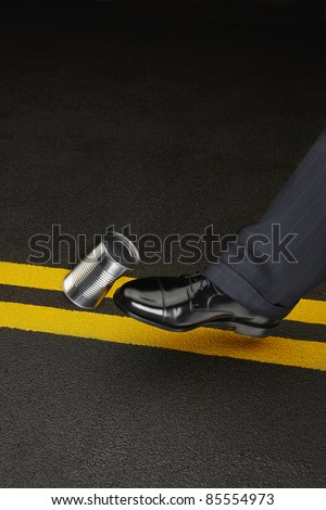 close up of politicians shoe kicking a dented shiny can down the road, space for copy - stock photo