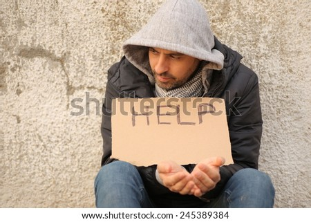 Close up of poor young guy with cartboard sign seeking help