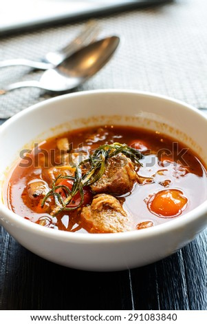 Close up of Pork stew in white bowl on wooden table