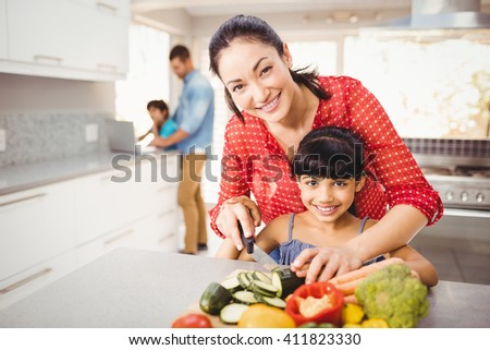 Close-up of portrait of happy mother teaching daughter to cut vegetables at home - stock photo