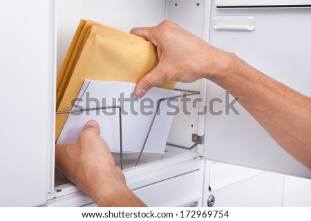 Close-up Of Postman's Hand Keeping Letters In Mailbox - stock photo