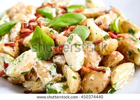 Close up of potato salad from boiled young potatoes with yoghurt and mayonnaise dressing, roasted bacon, sliced green onions and basil leaves in white plate. Fork, spoon and bunch of basil near it. - stock photo