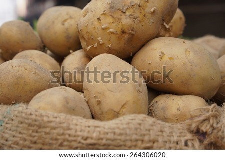 Close up of potatoes in the bag at the market with some potatoes in soft focus and blurry - stock photo