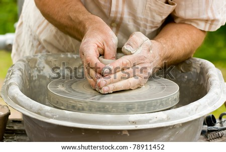 Close-up of potter's hands turning clay on a potter's wheel.