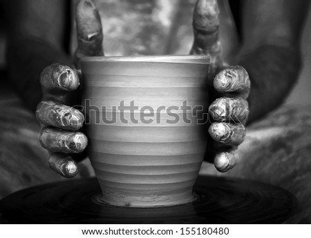 Close-up of potter's hands with the product on a potter's wheel - stock photo