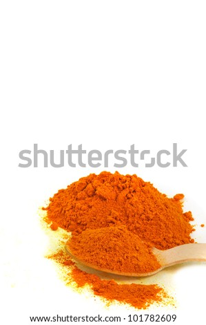 close up of powdered turmeric in a wooden spoon