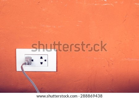 Close up of power plug plugged in a wall socket - stock photo