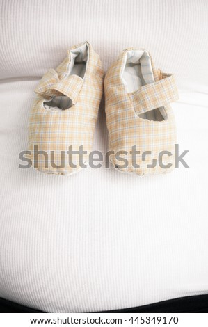 Close up of pregnant woman with green-white baby shoes on tummy - Color effect - stock photo