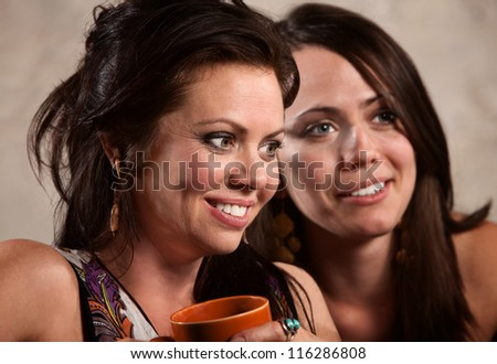 Close up of pretty friends sitting together - stock photo