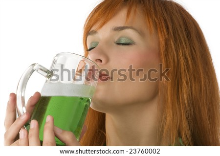 close up of pretty redhead girl drinking green beer as usual in saint patrick day