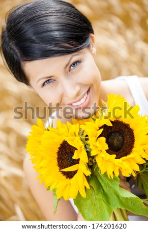 Close up of pretty woman with sunflowers in the rye field - stock photo