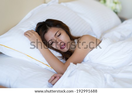 Close-up of pretty young lady sleeping in her bed - stock photo