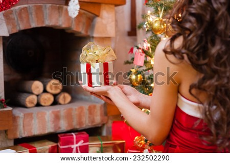 Close-up of pretty young woman in red and white christmas dress and long beautiful hair, holding a gift box near chimney and Christmas tree over living room. - stock photo