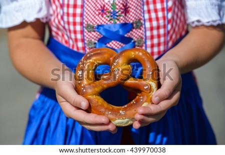 Close up of pretzel in the girl hands wearing a traditional bavarian dress dirndl during Oktoberfest in Germany . - stock photo