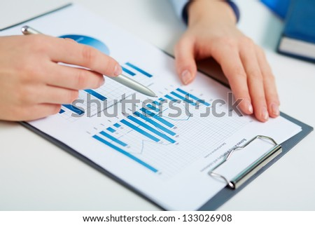 Close-up of printed statistics analyzed by a female business worker - stock photo