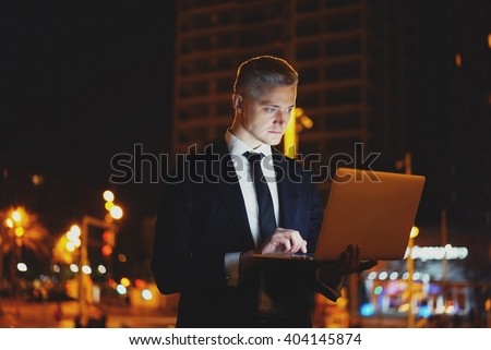 Close-up of professional businessman using laptop outdoors, successful male lawyer working on notebook computer and searching information in internet at night, city light - stock photo