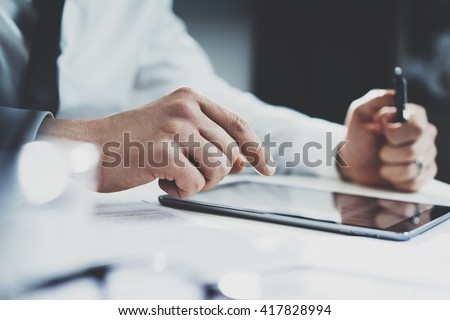 Close-up of professional businessman using modern digital tablet at his office, doctor working on a tablet pc - stock photo