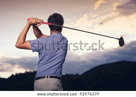 Close up of professional golf player in blue shirt teeing-off ball at sunset, view from behind. - stock photo