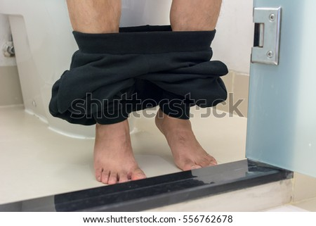 Close up of Pulled-down pants, man sitting in the toilet of house. Detail of the legs of a man sitting on toilet bowl. Pants down with bare foot man on toilet