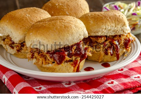 Close up of pulled pork barbeque sliders sitting on red heart napkin with bowl of coleslaw