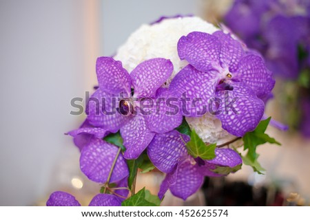 Close up of purple orchid wedding bouquet with rings on it - stock photo