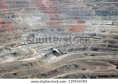 close up of quarry extracting iron ore with heavy trucks, excavators, diggers and locomotives - stock photo