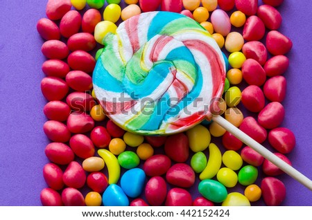 Close-up of rainbow lollipop on arranged candies.From above - stock photo