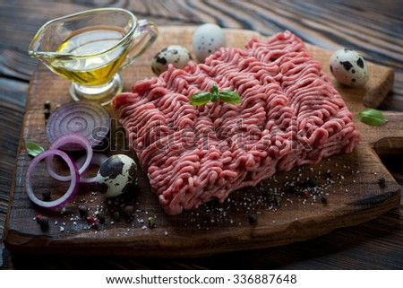 Close-up of raw ground beef meat with seasonings, studio shot - stock photo