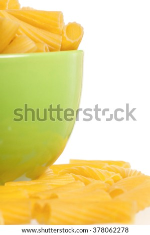 Close up of raw pasta in bowl isolated on white background