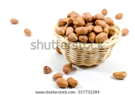 Close up of raw peanuts in basket on white background