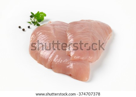 close up of raw turkey breasts with spice and herbs on white background