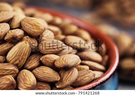 Close up of raw whole almonds in bowl and wooden spoon against a rustic background.