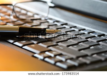 Close up of reading glasses and fountain pen on a laptop - stock photo