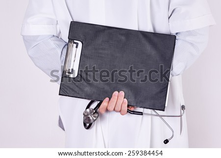 Close up of rear doctor  holding stethoscope and clipboard in  hands. Medical concept. - stock photo