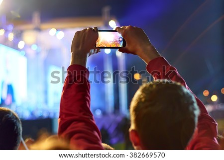 Close up of recording video with smartphone during a concert. - stock photo