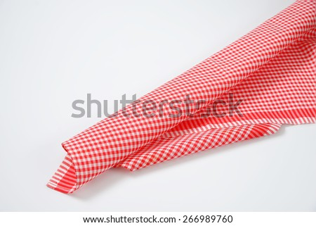 close up of red and white checkered dishtowel on white background