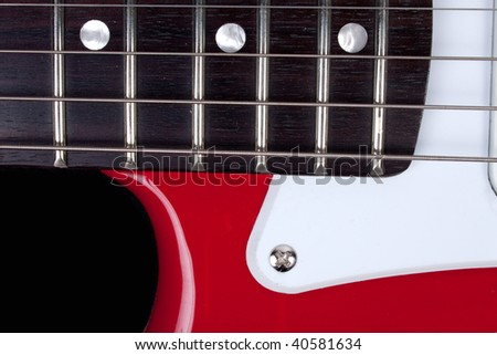 Close-up of red and white guitar neck, strings and body