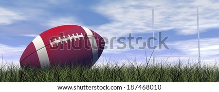 Close up of red and white rugby on green grass with two posts in the background - stock photo