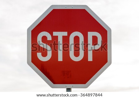 Close up of red and white stop sign in front of obscure building outdoors - stock photo