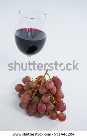 Close-up of red bunch of grapes with glass of red wine on white background