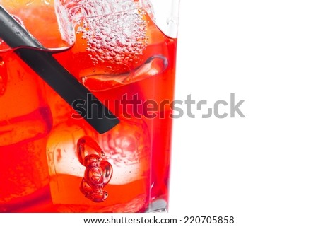 close-up of red cocktail with ice cubes and straw on white background, with space for text - stock photo