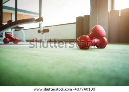 Close up of red dumbbell exercise weights on the green floor at fitness gym. - stock photo
