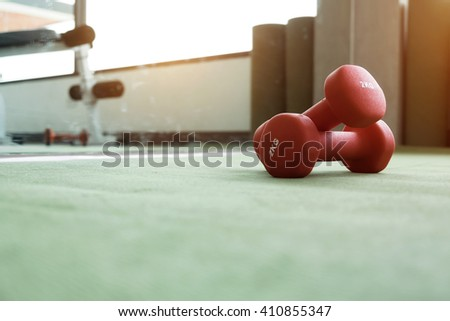 Close up of red dumbbell exercise weights on the green floor at fitness gym.