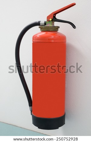 Close-up Of Red Fire Extinguisher Mounted On Wall - stock photo